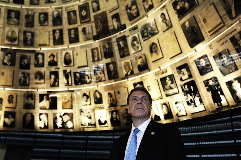 The Governor of New York Andrew Cuomo looks at pictures of Jewish Holocaust victims, at the Hall of Names during his visit to the Yad Vashem Holocaust Memorial museum (AFP Photo/MENAHEM KAHANA)