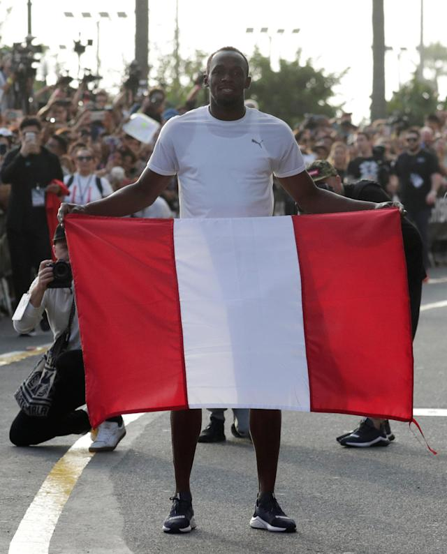 Usain Bolt poses with the Peruvian flag after competing in a race against a motorcycle taxi as part of a sponsored event in Lima, Peru - April 2, 2019 REUTERS/Henry Romero