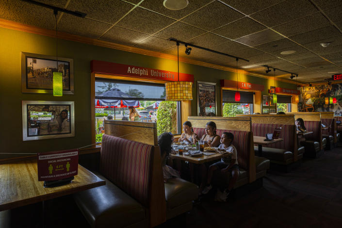 Patrons dine at an Applebee's Bar & Grill where half the booths were roped off for social distancing, in Westbury, N.Y., June 24, 2020. (Hiroko Masuike/The New York Times).