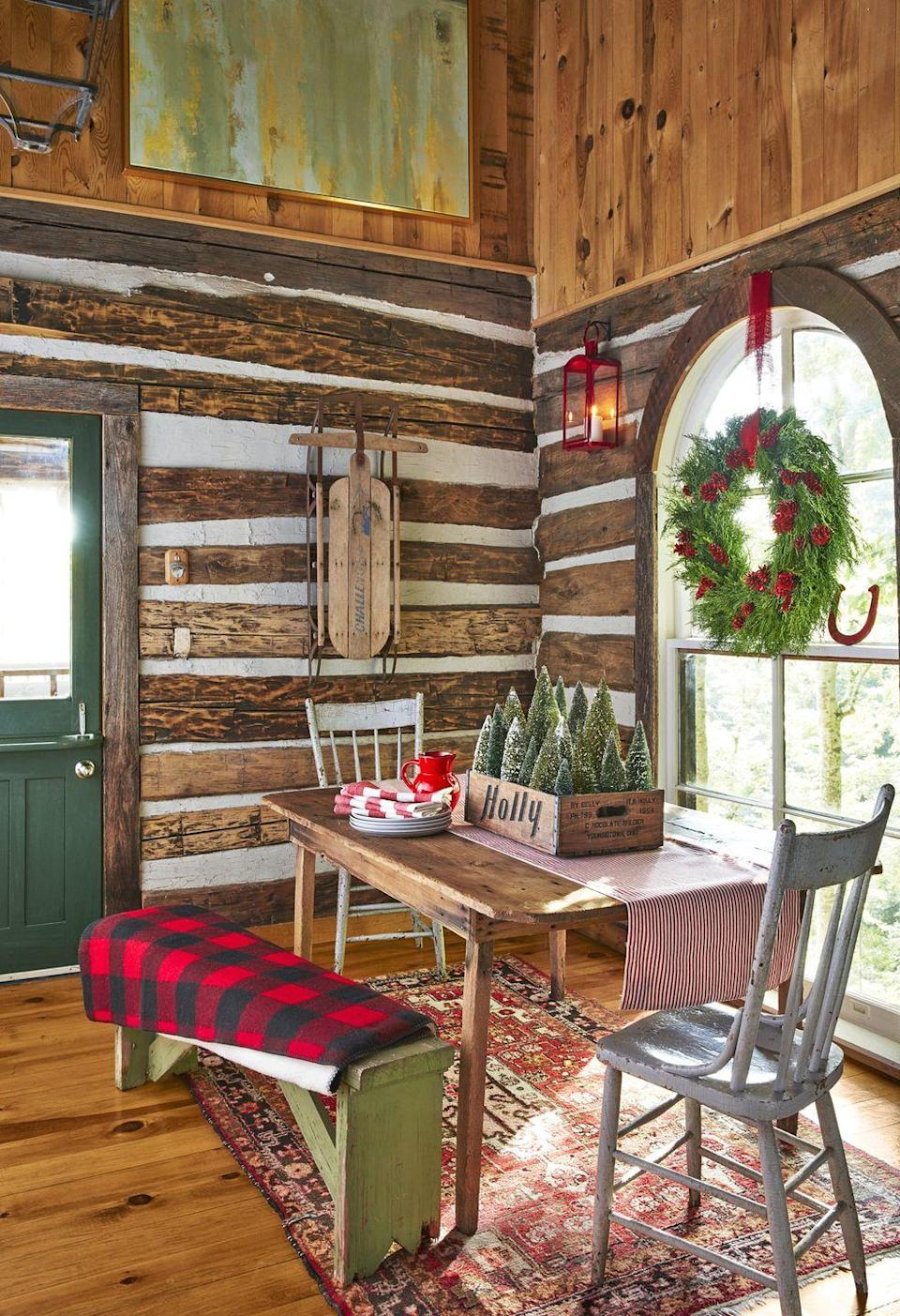 """<p>Singer-songwriter Holly Williams, the owner of this Tennessee farmhouse, uses a 1960s Holly Beverage Co. soda crate filled with <a href=""""https://www.countryliving.com/home-design/g2800/bottlebrush-trees-christmas-decorating-ideas/"""" rel=""""nofollow noopener"""" target=""""_blank"""" data-ylk=""""slk:bottle brush trees"""" class=""""link rapid-noclick-resp"""">bottle brush trees</a> to add festive cheer to her dining nook.<br></p><p><a class=""""link rapid-noclick-resp"""" href=""""https://www.amazon.com/AerWo-Artificial-Christmas-Bottle-Ornaments/dp/B07FDGB77K?tag=syn-yahoo-20&ascsubtag=%5Bartid%7C10050.g.1247%5Bsrc%7Cyahoo-us"""" rel=""""nofollow noopener"""" target=""""_blank"""" data-ylk=""""slk:SHOP BOTTLE BRUSH TREES"""">SHOP BOTTLE BRUSH TREES</a></p>"""