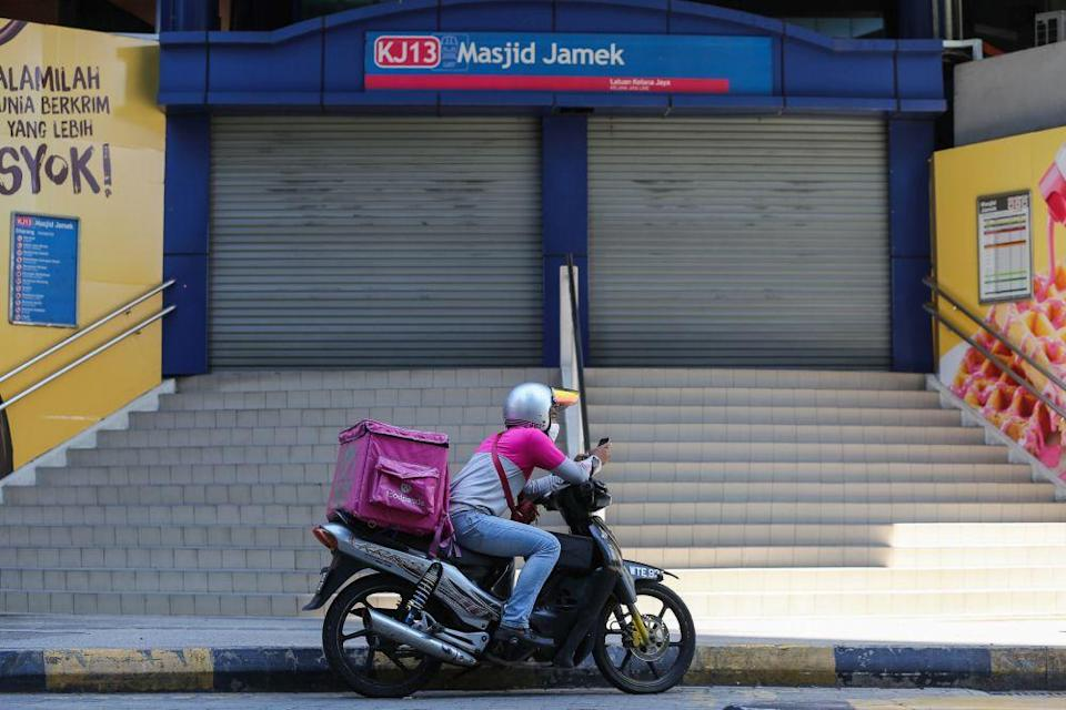A Foodpanda rider idles in front of the Masjid Jamek LRT station in Kuala Lumpur on day eight of the movement control order March 25, 2020. — Picture by Yusof Mat Isa