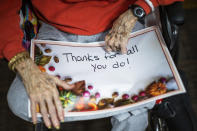 A nursing home resident holds a sign addressed to the staff before a small Thanksgiving Day parade with nurses, other staff and residents at the Hebrew home at Riverdale in the Bronx, Thursday, Nov 26, 2020, in New York.(AP Photo/Eduardo Munoz Alvarez)