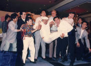 """In this undated photo released by Radio Television Hong Kong (RTHK), Hong Kong DJ, Ray Cordeiro, also known as Uncle Ray, center, attends a celebration party after being awarded the Member of the Order of the British Empire in 1987 in Hong Kong. After more than seven decades in radio, the 96-year-old Hong Kong DJ bid farewell to his listeners Saturday, May 15, 2021 with """"Time to Say Goodbye,"""" sung by Sarah Brightman and Andrea Bocelli. (Radio Television Hong Kong via AP)"""