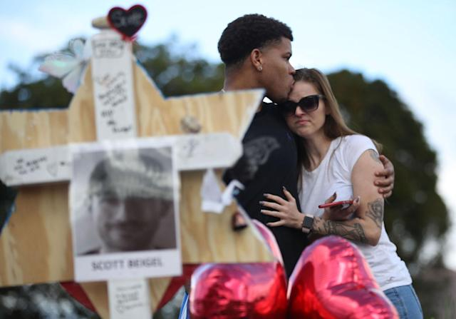 <p>Ashley Boul and Joel Robinson (L), who is an alumni of Marjory Stoneman Douglas High School, visit a makeshift memorial setup in front of the school on February 19, 2018 in Parkland, Fla. (Photo: Joe Raedle/Getty Images) </p>