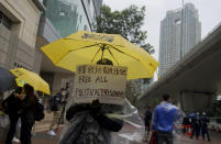 A supporter holds an umbrella and a placard outside a court in Hong Kong, Thursday, March 4, 2021. A marathon court hearing for 47 pro-democracy activists in Hong Kong charged with conspiracy to commit subversion enters its fourth day on Thursday, as the court deliberates over whether the defendants will be granted bail. (AP Photo/Vincent Yu)