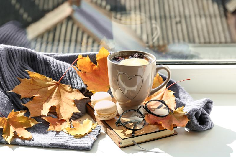 Cup of aromatic tea with book, warm sweater and autumn leaves on windowsill