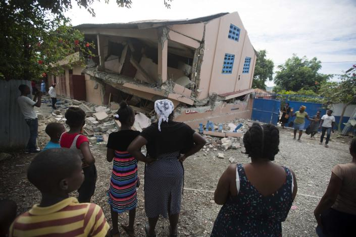 Residents stand looking at a collapsed school damaged by a magnitude 5.9 earthquake the night before, in Gros Morne, Haiti, Sunday, Oct. 7, 2018. Emergency teams worked to provide relief in Haiti on Sunday after the quake killed at least 11 people and left dozens injured. (AP Photo/Dieu Nalio Chery)