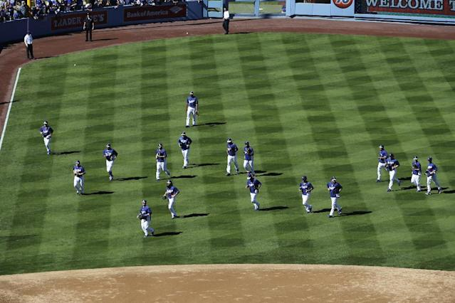 Los Angeles Dodgers players run on the field during warm-ups before Game 3 of the National League Division Series against the Atlanta Braves, Sunday, Oct. 6, 2013, in Los Angeles. (AP Photo/Jae C. Hong)