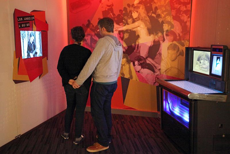 """This March 26, 2012 photo shows visitors watching a display about the 1960s 'Go-Go' scene in Los Angeles, next to a vintage Rock-Ola jukebox converted to digital use, at the exhibit, """"Trouble In Paradise: Music and Los Angeles, 1945-1975,"""" at the Grammy Museum in Los Angeles. The museum website says the exhibit focuses on the """"tensions between alluring myths of Southern California paradise and the realities of social struggle that characterized the years following WWII."""" (AP Photo/Reed Saxon)"""