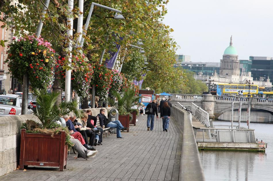 People relax on the riverfront in Dublin.