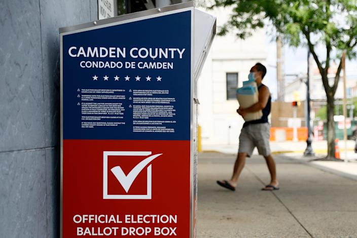A man walks past a vote-by-mail drop box for the upcoming New Jersey primary election outside the Camden, N.J., Administration Building, Wednesday, July 1, 2020. (AP Photo/Matt Slocum)
