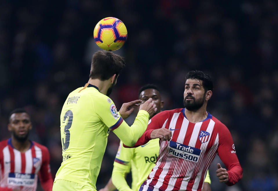 Athletico Madrid's Diego Costa, right, duels for the ball with Barcelona's Gerard Pique during a Spanish La Liga soccer match between Atletico Madrid and FC Barcelona at the Metropolitano stadium in Madrid, Saturday, Nov. 24, 2018. (AP Photo/Manu Fernandez)