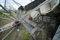 Mike Gaines, a deckhand, sits on the overturned and destroyed shrimp trawler that provides his living, in the aftermath of Hurricane Ida in Plaquemines Parish, La., Monday, Sept. 13, 2021. (AP Photo/Gerald Herbert)