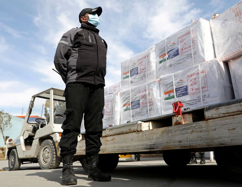 FILE PHOTO: An Indian security personnel stands guard neax to the boxes containing vials of COVISHIELD, a coronavirus disease (COVID-19) vaccine donated by Indian government in Kabul