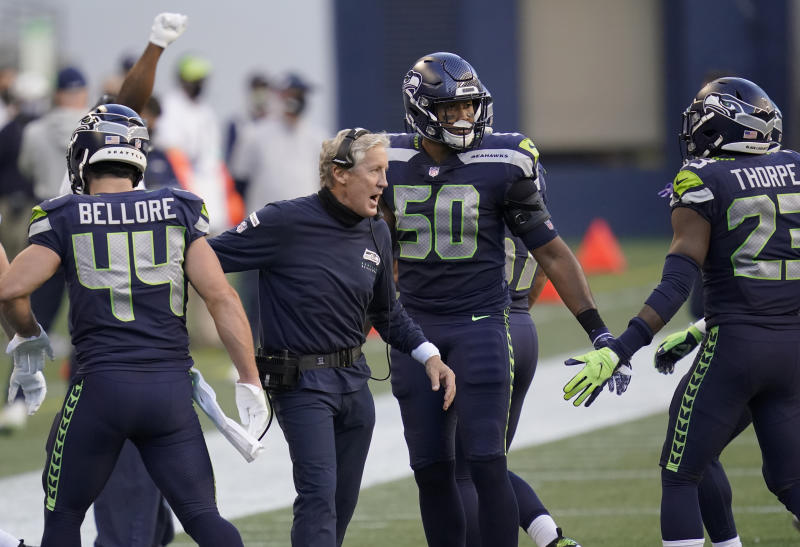 Pete Carroll celebrates with his players, sans mask.