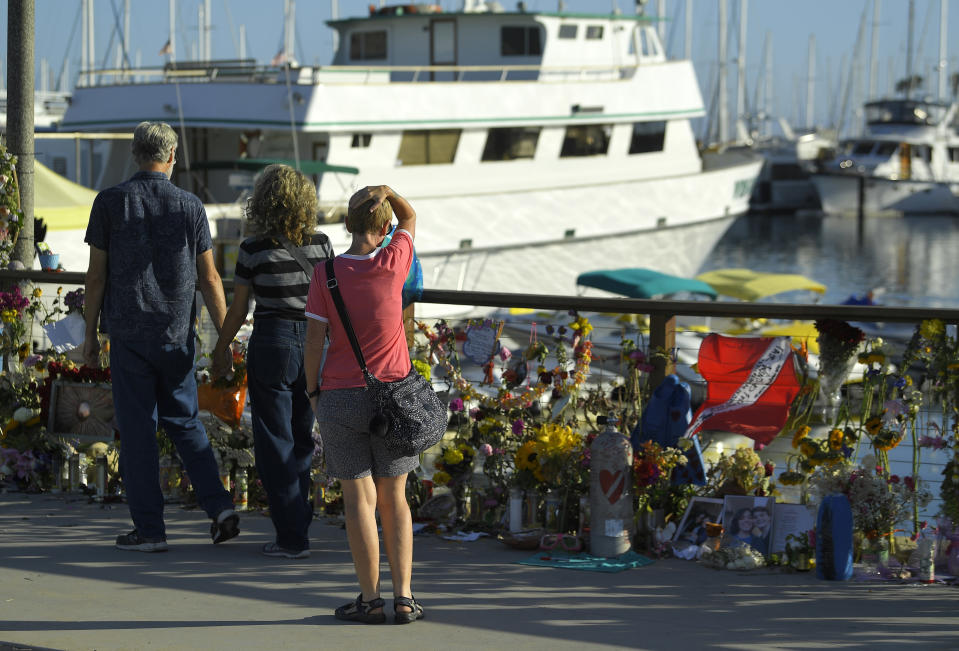 FILE - In this Sept. 6, 2019, file photo, people visit a growing memorial to the victims who died aboard the dive boat Conception as its sister boat Vision sits in the background, in Santa Barbara, Calif. The captain of a scuba diving boat that burned and sank off the California coast, killing 34 people below deck, has pleaded not guilty to federal manslaughter charges. Jerry Boylan surrendered Tuesday, Feb. 16, 2021, and was arraigned in Los Angeles federal court on 34 counts of seaman's manslaughter. (AP Photo/Mark J. Terrill, File)