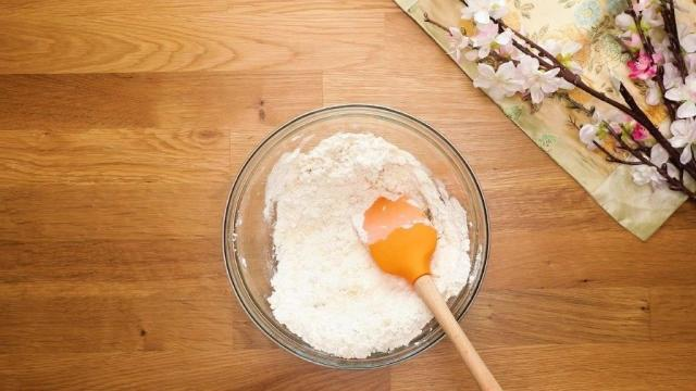 Mixed flour and cooking oil in glass bowl with spatula
