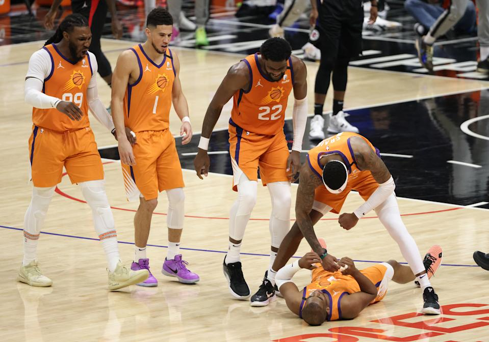 The Suns rush to help 36-year-old star Chris Paul off the floor during his historical playoff run. (Harry How/Getty Images)
