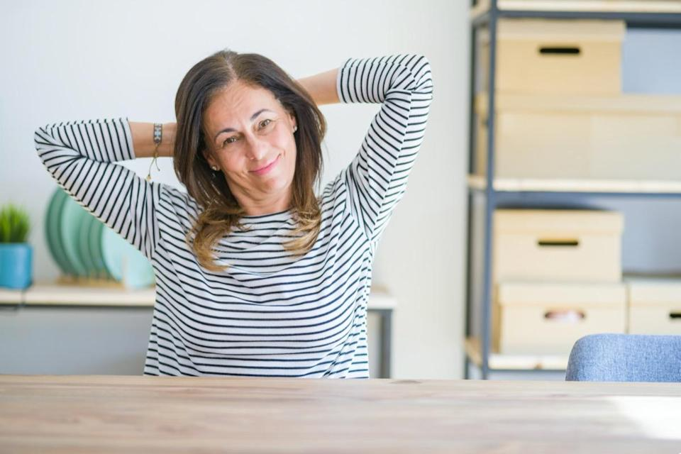 Middle age senior woman sitting at the table at home relaxing and stretching, arms and hands behind head and neck smiling happy