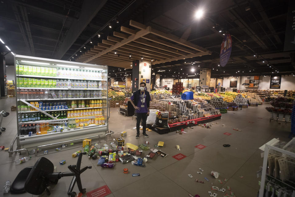An employee stands inside a Carrefour supermarket after protesters entered knocking products off shelves and overturning carts in protest against the murder of Black man Joao Alberto Silveira Freitas at a different Carrefour supermarket the night before, on Brazil's National Black Consciousness Day in Sao Paulo, Brazil, Friday, Nov. 20, 2020. Freitas died after being beaten by supermarket security guards in the southern Brazilian city of Porto Alegre, sparking outrage as videos of the incident circulated on social media. (AP Photo/Andre Penner)