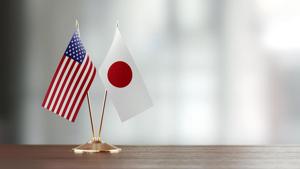 Japanese and American flag pair on desk over defocused background. Horizontal composition with copy space and selective focus.