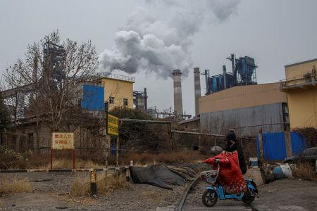 A woman rides a scooter past a steel plant in Anyang, Henan province, China, February 18, 2019.   REUTERS/Thomas Peter