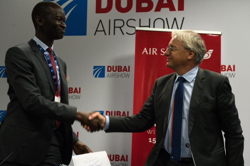 Air Senegal CEO Ibrahima Kane, left, shakes hands with Airbus' chief commercial officer Christian Scherer at a news conference at the Dubai Airshow in Dubai, United Arab Emirates, Tuesday, Nov. 19, 2019. Air Senegal said Tuesday it will purchase eight Airbus A220 aircraft. (AP Photo/Jon Gambrell)