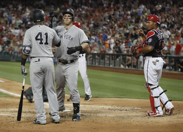 New York Yankees' Tyler Austin (26) is greeted by teammate Miguel Andujar (41) after hitting a two-run home run off Washington Nationals Gio Gonzalez during the fourth inning of an interleague baseball game against the New York Yankees at Nationals Park, Tuesday, May 15, 2018, in Washington. Looking on is Washington Nationals catcher Pedro Severino (29). (AP Photo/Pablo Martinez Monsivais)