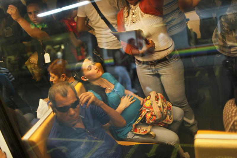 In this March 14, 2013 photo, Lady Laura Rosalez, 21, who is seven-months pregnant, rests while traveling via subway in Caracas, Venezuela. Politics rule everyday government in Venezuela, from state oil company to subways. State companies such as oil producer PDVSA and the manager of Caracas' subway system used to be known around the world for their professionalism. In recent years, many of those companies have seen service and revenue deteriorate as political cadres rather than engineers were brought in to run everything from oil exploration to mass transit. (AP Photo/Rodrigo Abd)