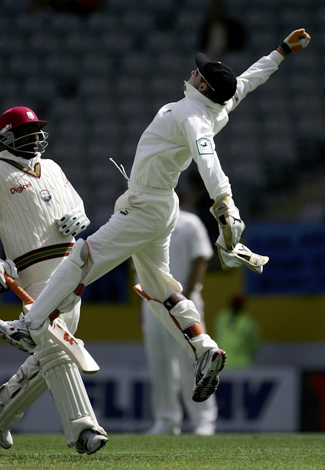 AUCKLAND, NEW ZEALAND - MARCH 10:  Brendon McCullum of New Zealand fields the ball as Dwayne Bravo makes his ground during day two of the first test match between New Zealand and the West Indies at Eden Park March 10, 2006 in Auckland, New Zealand.  (Photo by Phil Walter/Getty Images)