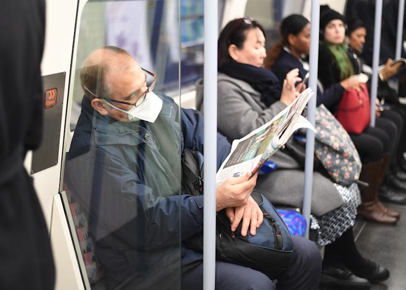 A man on the Jubilee line on the London Underground tube network wearing a protective facemask.