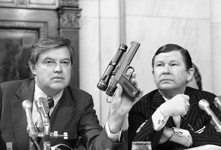 "<div class=""inline-image__caption""><p>Chairman Frank Church, D-ID, holds up a poison dart gun as co-chairman John G. Tower, R-TX looks at the weapon.</p></div> <div class=""inline-image__credit"">Henry Griffin/AP</div>"
