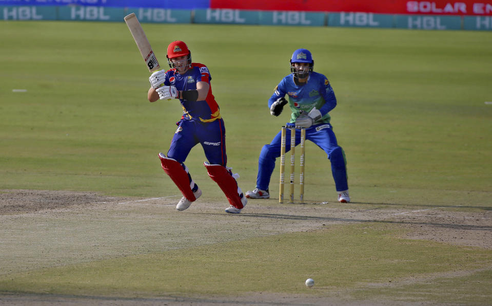 Karachi Kings' Joe Clarke, center, plays a shot while Multan Sultans' Mohammad Rizwan watches during a Pakistan Super League T20 cricket match between Karachi Kings and Multan Sultans at the National Stadium, in Karachi, Pakistan, Saturday, Feb. 27, 2021. (AP Photo/Fareed Khan)