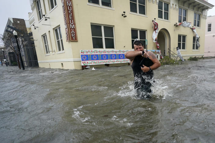 Trent Airhart wades through flood waters, Wednesday, Sept. 16, 2020, in downtown Pensacola, Fla. Hurricane Sally made landfall Wednesday near Gulf Shores, Alabama, as a Category 2 storm, pushing a surge of ocean water onto the coast and dumping torrential rain that forecasters said would cause dangerous flooding from the Florida Panhandle to Mississippi and well inland in the days ahead.(AP Photo/Gerald Herbert)