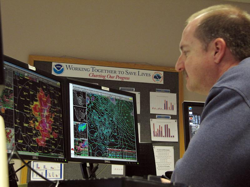 In a Jan. 10, 2013 photo, Richard Emanuel, a National Weather Service forecaster in Cheyenne, Wyo., looks at radar images of a storm as it dumps heavy snow on the western plains and Black Hills. This winter, the Weather Service is trying out simple, descriptive language to possibly replace its 14 watches, advisories and warnings for wintry weather _ from ice storms to blizzards, wind chill to lake-effect snow. (AP Photo/Mead Gruver)