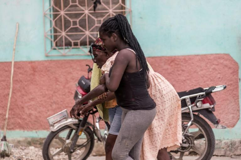 An old woman is helped by a relative near Camp-Perrin, Haiti on August 16, 2021