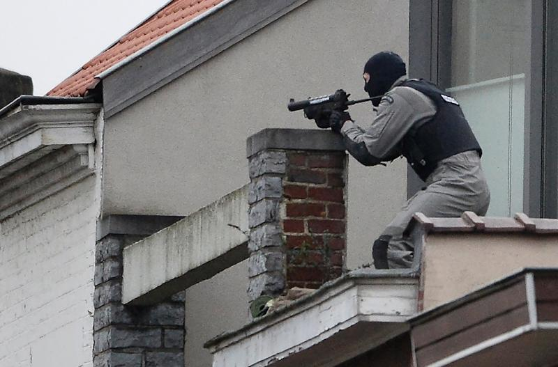 A member of the special forces takes position on a roof near the site of a shooting in the southern Forest district of Brussels, on March 15, 2016