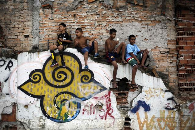 """Children watch a soccer match held by activists as part of the """"Rebel Cup"""" in downtown Sao Paulo April 13, 2014. The """"Rebel Cup"""" is an informal tournament bringing together social movements as a way of protest against government spending for the 2014 World Cup in Brazil. The boy (L) wears a T-shirt of Real Madrid and the boy (2nd R) wears the shorts of Barcelona. REUTERS/Nacho Doce (BRAZIL - Tags: SPORT SOCCER WORLD CUP POLITICS)"""