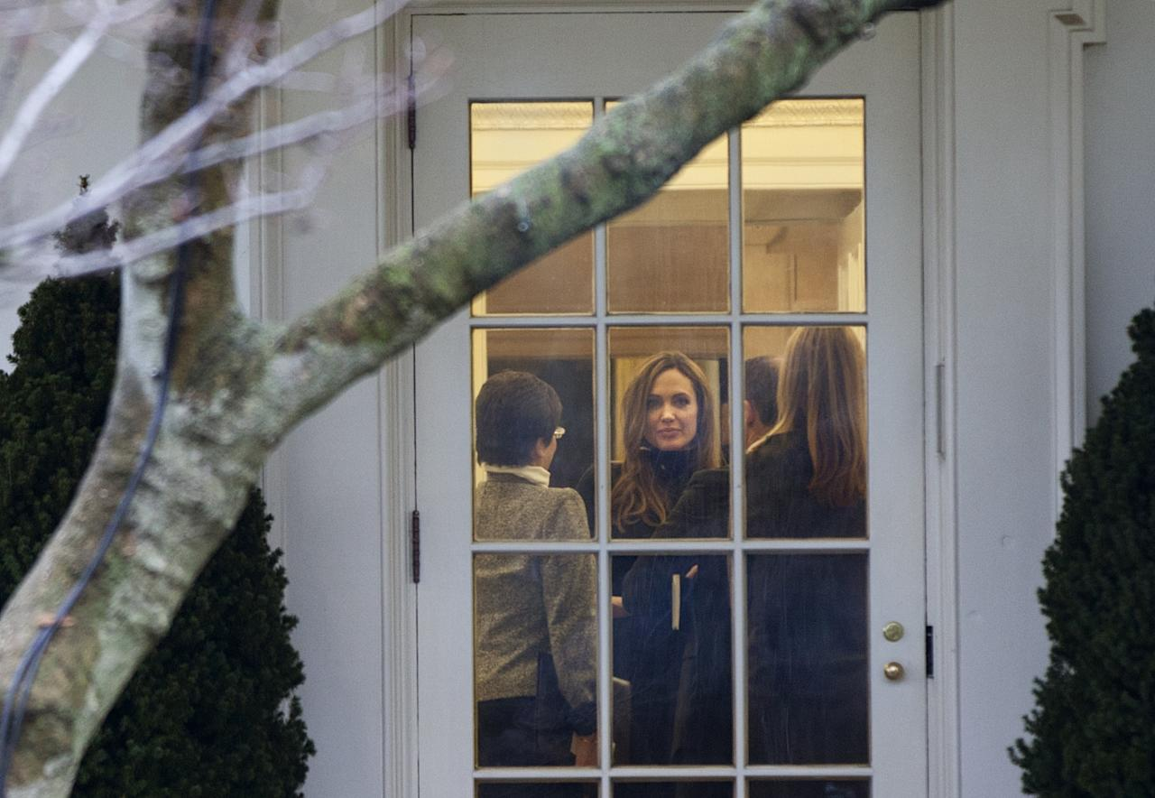 "WASHINGTON - JANUARY 11:  Actress Angelina Jolie (2nd L) looks out from the Oval Office of the White House after a meeting January 11, 2012 in Washington, DC.  Angelina Jolie was in Washington to attend the premiere of her directorial debut ""In the Land of Blood and Honey"" at the Holocaust Museum.  (Photo by Brendan Smialowski/Getty Images)"