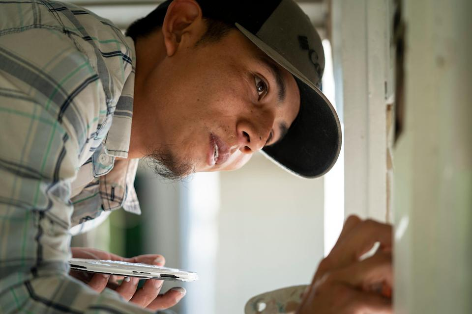 Francis Portillo paints windows at a home before an inspection in Jacksonville, Fla., on April 8.