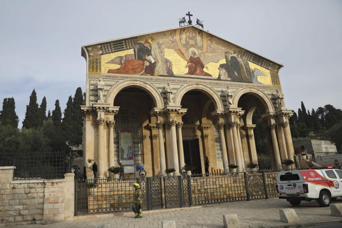 """An firefighter stands outside the Church of All Nations in the Garden of Gethsemane, in east Jerusalem, Friday, Dec. 4, 2020. Israeli police said Friday they arrested a Jewish man after he poured out a """"flammable liquid"""" inside a church near Jerusalem's Old City, in what they described as a """"criminal"""" incident. (AP Photo/Mahmoud Illean)"""