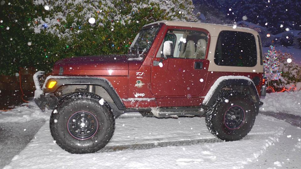 Comox, BC Canada Dec, 2017 Jeep Wrangler TJ 2001 evening photo with snow dropping and background of some Christmas lights.