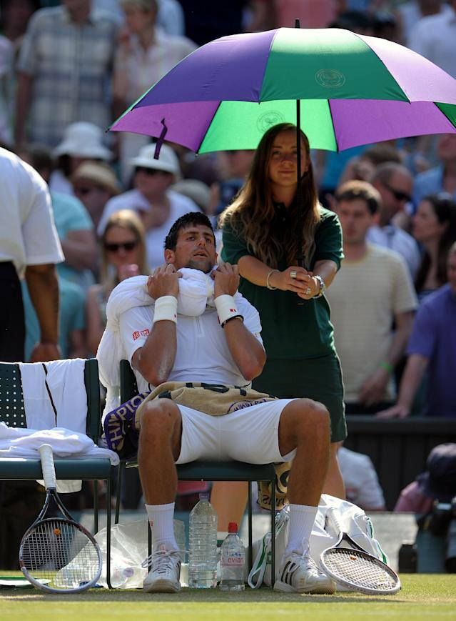Serbia's Novak Djokovic sits with a towel of ice on his head during a break of ends in his match against Great Britain's Andy Murray on day thirteen of the Wimbledon Championships at The All England Lawn Tennis and Croquet Club, Wimbledon.