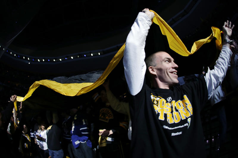 David Chirgwin, of Malden, Mass. helps pass a large Boston Bruins banner around the arena before Game 2 of a first-round NHL hockey playoff series between the Boston Bruins and the Toronto Maple Leafs in Boston, Saturday, May 4, 2013. (AP Photo/Elise Amendola)