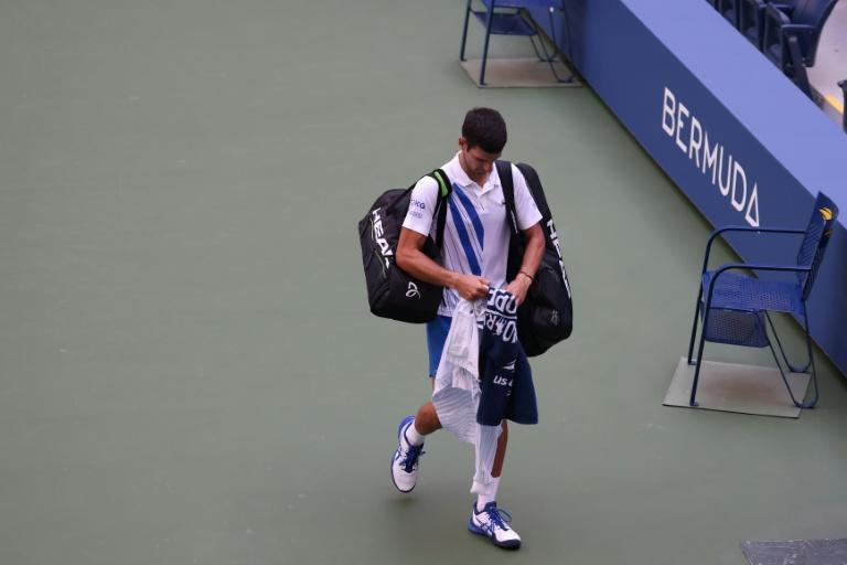Novak Djokovic walks off the court after being defaulted for inadvertently striking a line judge with a ball at the US Open on Sunday