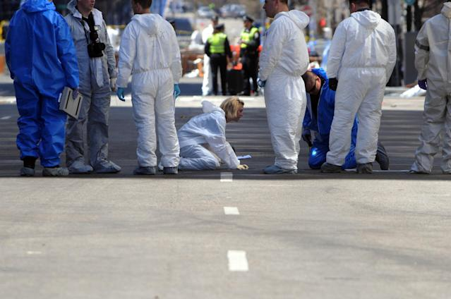 BOSTON, MA - APRIL 17: FBI crime scene investigators sweep up Boylston Street after placing an evidence marker just past Berkeley Street April 17, 2013 in Boston, Massachusetts. Investigators continue to work the scene of two bomb explosions at the finish line of the marathon that killed 3 people and injured over one hundred more. (Photo by Darren McCollester/Getty Images)