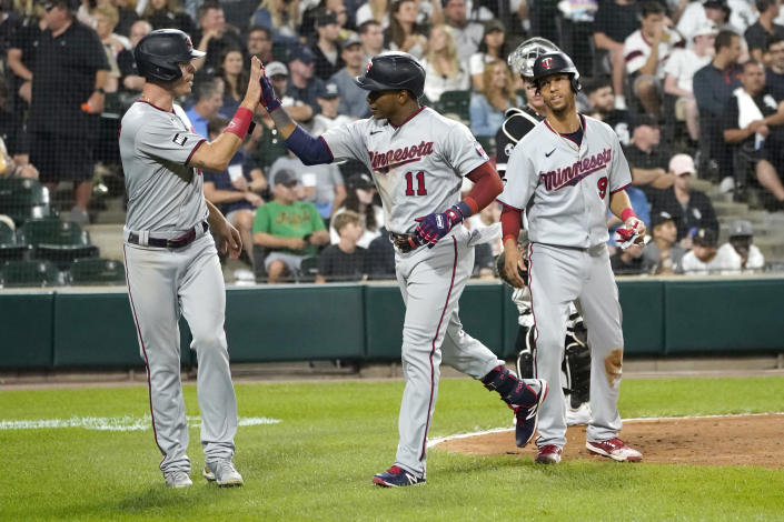 Minnesota Twins' Jorge Polanco (11) celebrates his three-run home run off Chicago White Sox relief pitcher Codi Heuer, with Max Kepler, left, and Andrelton Simmons, during the sixth inning of a baseball game Wednesday, July 21, 2021, in Chicago. (AP Photo/Charles Rex Arbogast)