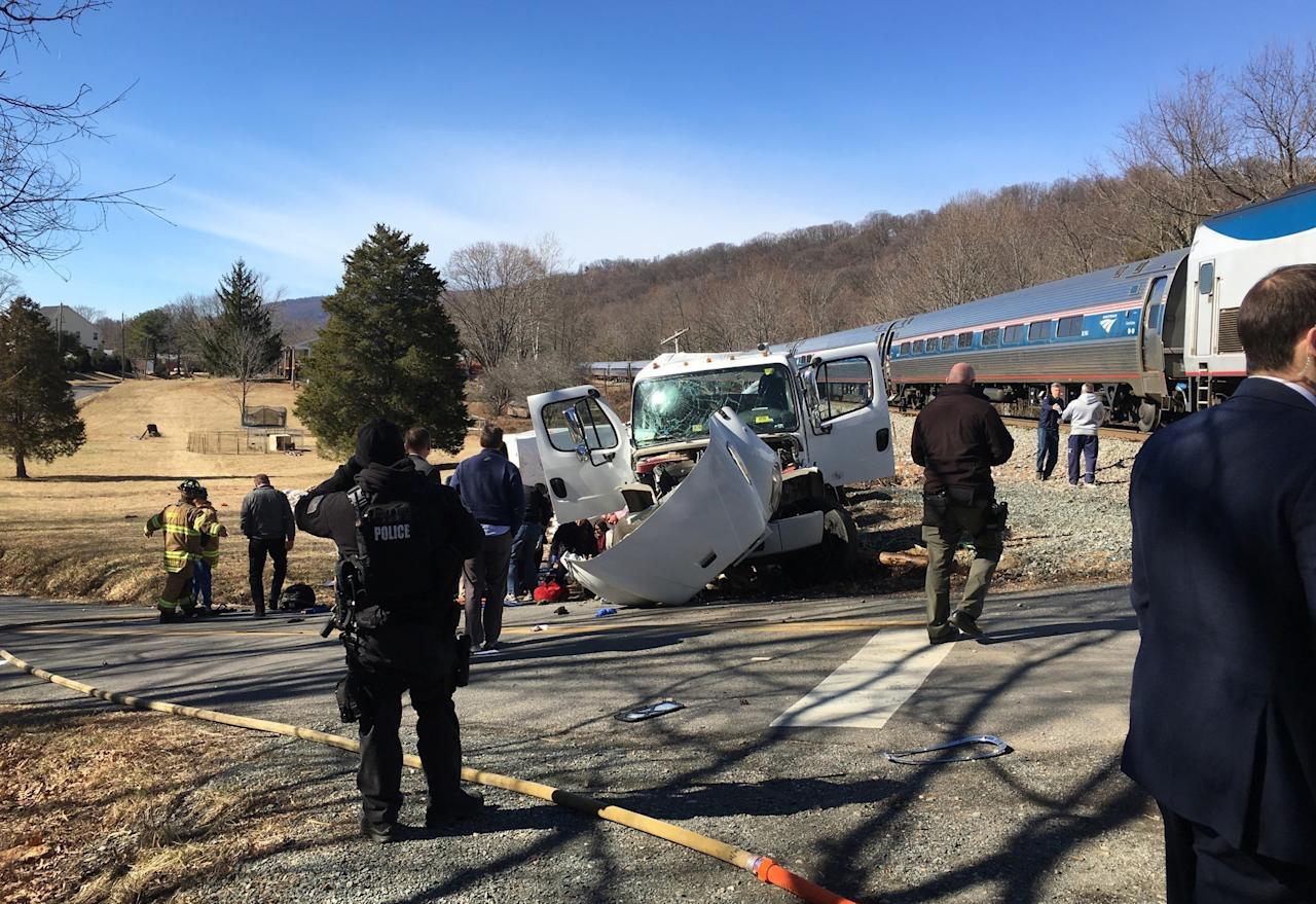 <p>This photo provided by Rep. Bruce Poliquin, R-Maine shows emergency personnel standing near a chartered train carrying members of Congress after it hit a garbage truck in Crozet, Va., Jan. 31, 2018. (Photo: Bruce Poliquin via AP) </p>