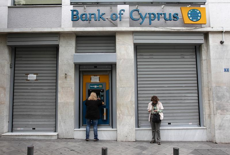 Customers of Bank of Cyprus use the ATM as the bank remains closed for the second day in central Athens on Wednesday, March 20, 2013. Banking stocks in Greece were hammered Tuesday before Cypriot lawmakers rejected a bailout plan, while government officials here urged eurozone countries to give the Mediterranean island more time to come up with a viable solution. (AP Photo/Thanassis Stavrakis)