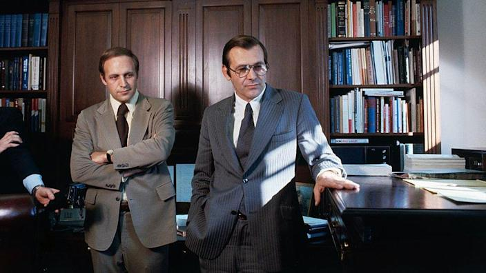 """Donald Rumsfeld fingers his """"stand-up"""" desk in White House office as he talks with his successor as White House Chief of Staff, Richard B. Cheney in 1975"""